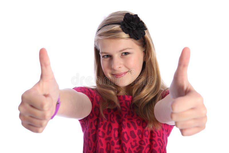 Os polegares acima da mão positiva assinam pela menina loura da escola foto de stock