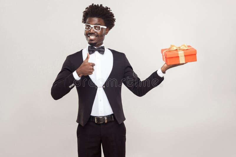 Os polegares africanos do homem levantam e guardando a caixa de presente imagem de stock royalty free