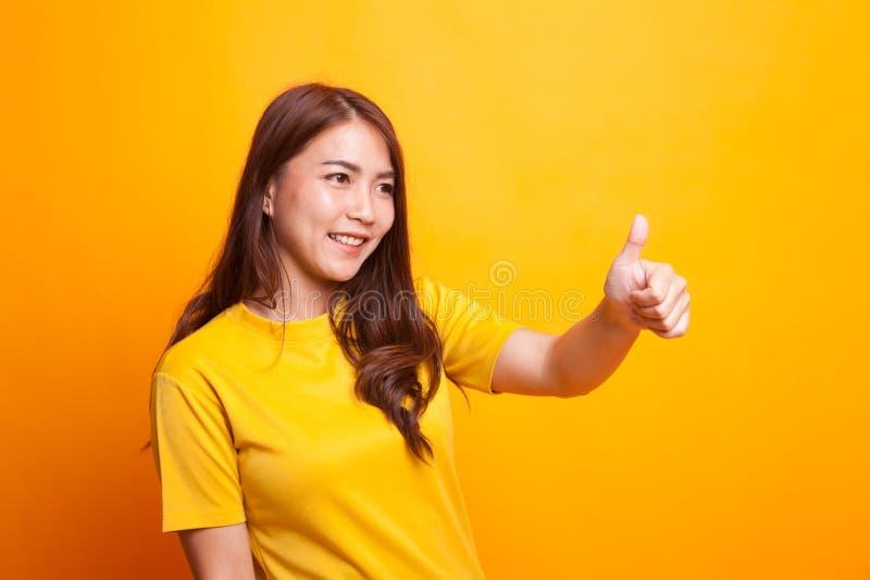 Os polegares asiáticos da mulher levantam e sorriem fotografia de stock