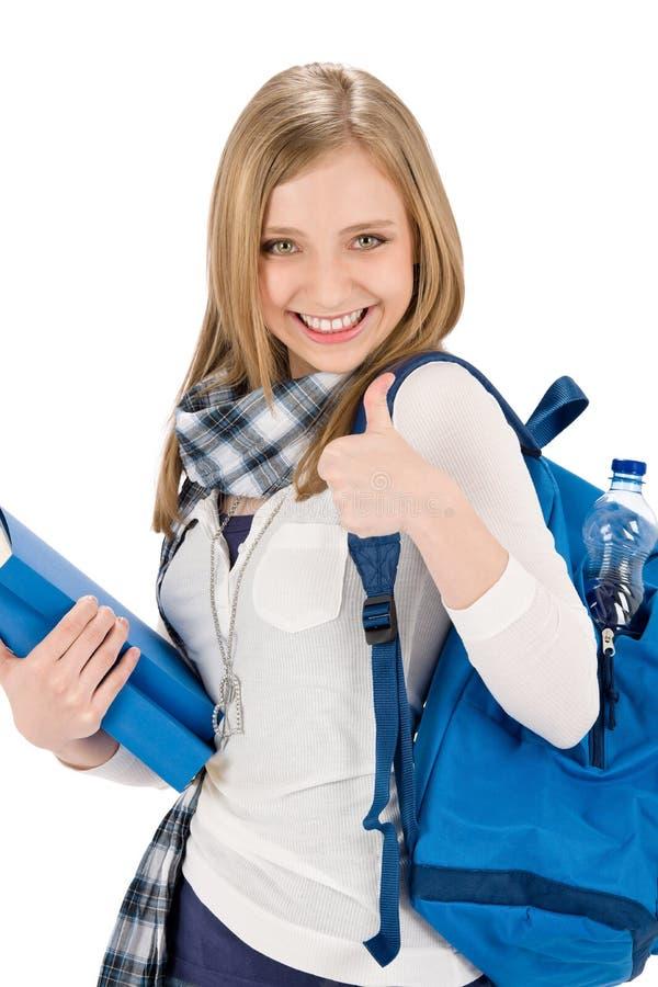 Os polegares levantam a mulher do adolescente do estudante com schoolbag imagens de stock royalty free