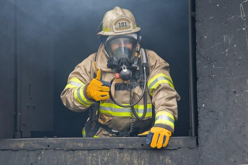 Os polegares levantam o sapador-bombeiro fotografia de stock
