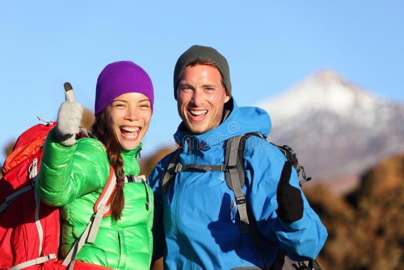 Os polegares levantam os caminhantes felizes que caminham na montanha imagens de stock royalty free