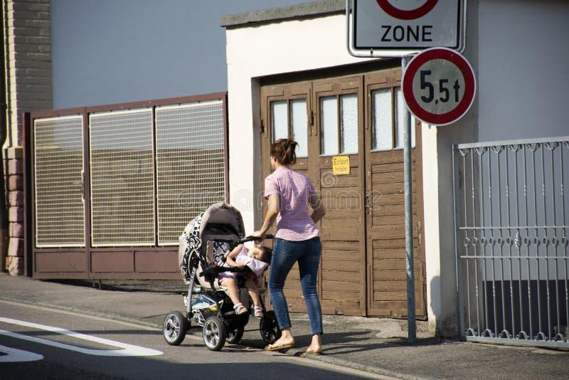 Os povos alemães da mãe empurram o transporte do carrinho de criança com o bebê no passeio imagens de stock