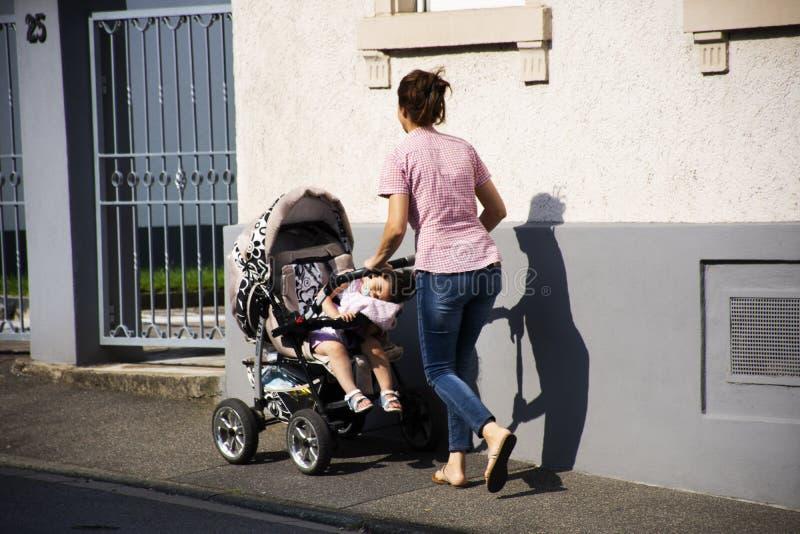 Os povos alemães da mãe empurram o transporte do carrinho de criança com o bebê no passeio fotos de stock