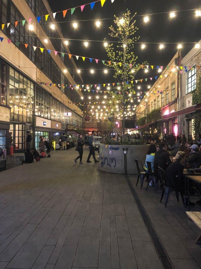 Os povos andam ao longo da rua pedestre moderna da noite com bandeiras e bulbos, boutiques com cafés Geórgia, Batumi, o 17 de abr imagens de stock