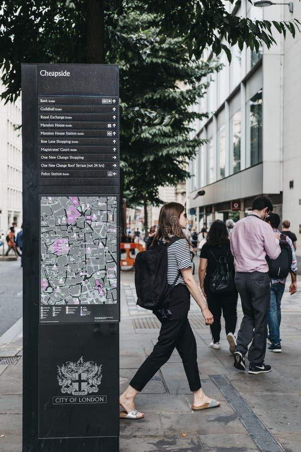 Os povos andam após sentidos e placa do mapa em Cheapside, cidade de Londres, Reino Unido fotos de stock