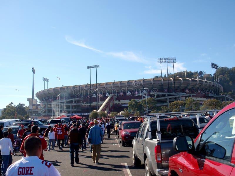 Os povos andam através do parque de estacionamento do castiçal ao estádio foto de stock royalty free