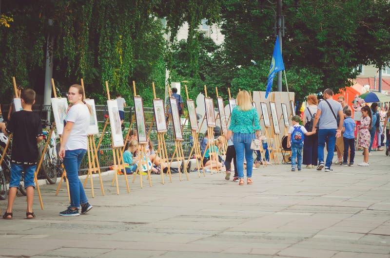 Os povos andam no parque na celebração do dia do ` s da cidade e olham a exposição do pa foto de stock royalty free