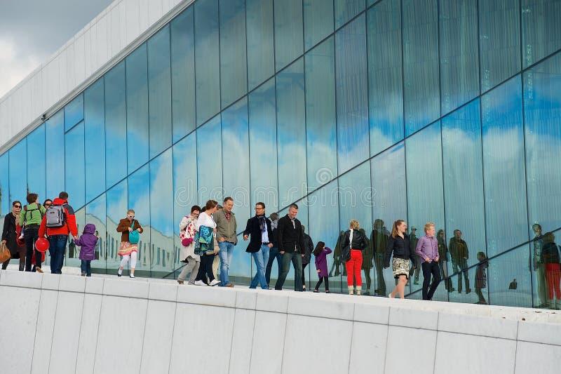 Os povos andam pela parede lateral da construção de teatro da ópera nacional de Oslo em Oslo, Noruega fotografia de stock