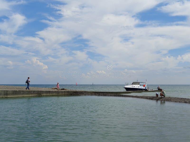 Os povos andam perto do mar, o barco no cais, nuvens bonitas foto de stock