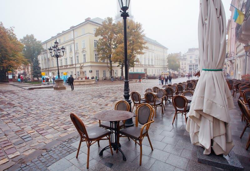 Os povos andam sob a chuva no mercado com ruas cobbled e esvaziam o café exterior imagens de stock royalty free