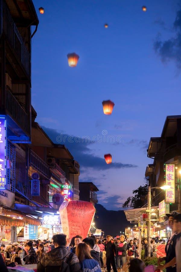 Os povos apreciam lançar a lanterna de papel com desejo da palavra em Pingxi imagens de stock