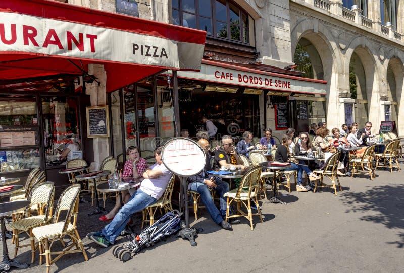 Os povos apreciam sentar-se no sol no café fotos de stock