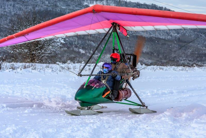 Os povos aprontam-se para fazer o voo no planador do motor do esqui no inverno no fundo nevado da floresta fotos de stock