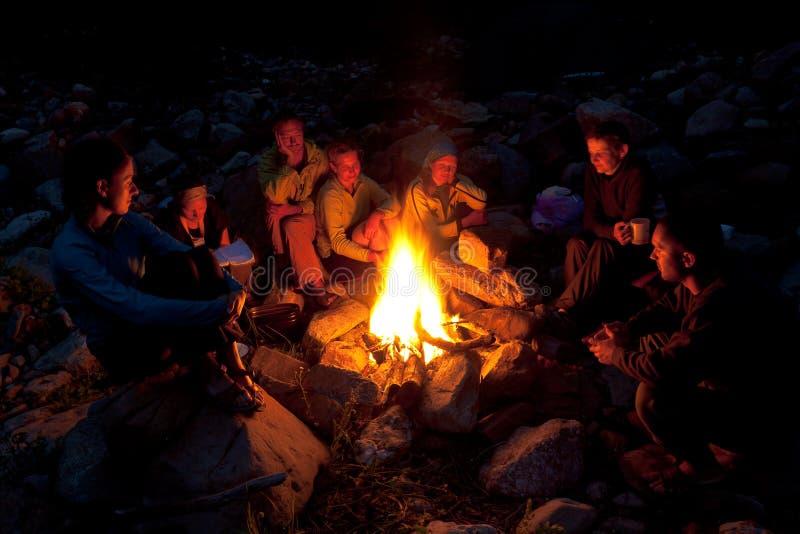 Os povos aproximam a fogueira na floresta. foto de stock royalty free