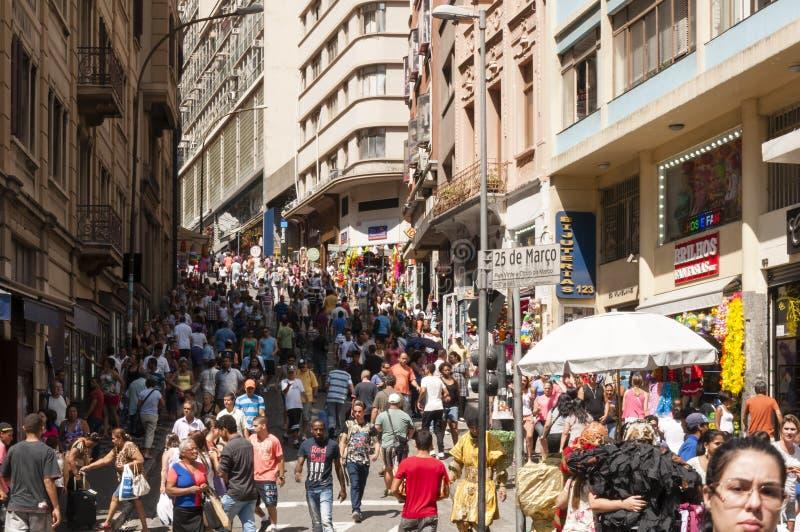 Os povos aproximam rua o 25 de março, cidade Sao Paulo, Brasil imagem de stock