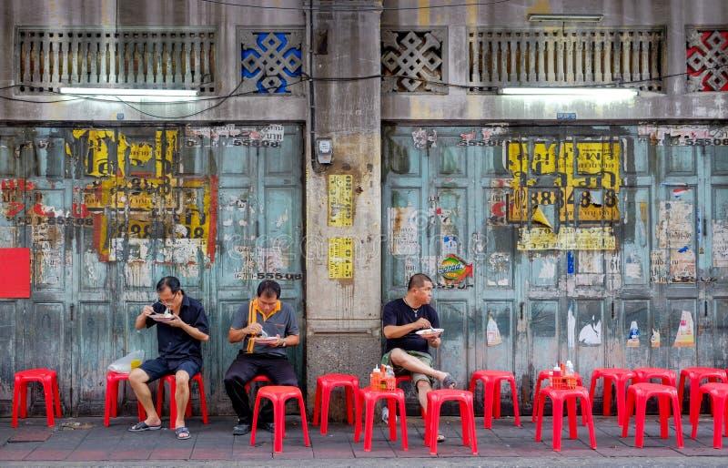 Os povos asiáticos tailandeses não identificados que são sentam-se na cadeira vermelha para comer o alimento da rua do arroz de c foto de stock