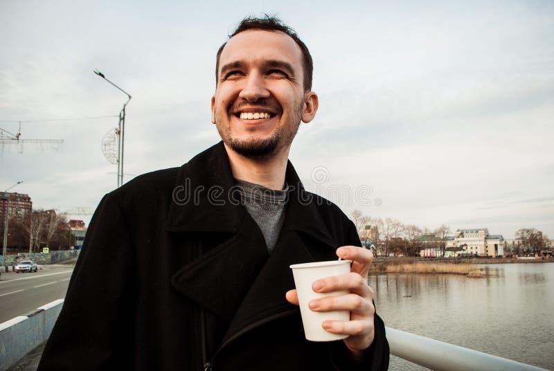 Os povos bebem o café na terraplenagem do rio fotografia de stock royalty free