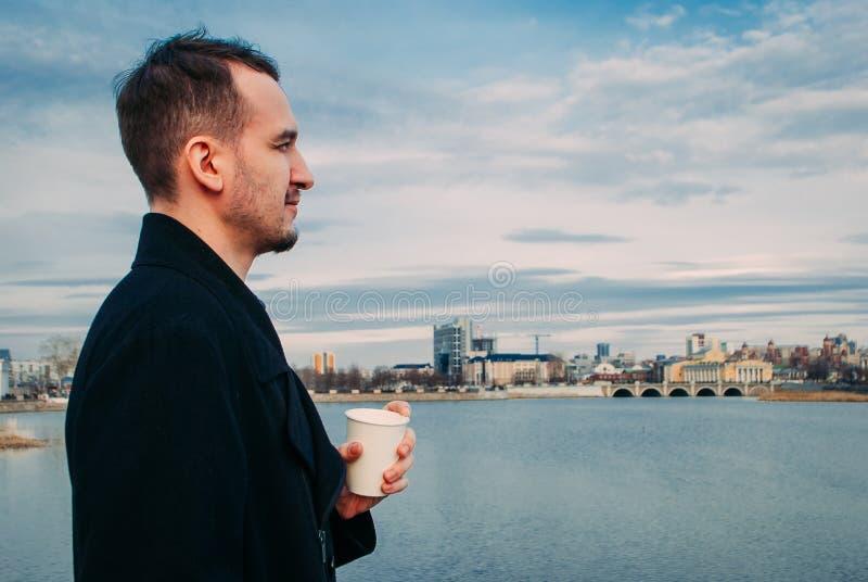 Os povos bebem o café na terraplenagem do rio fotos de stock royalty free