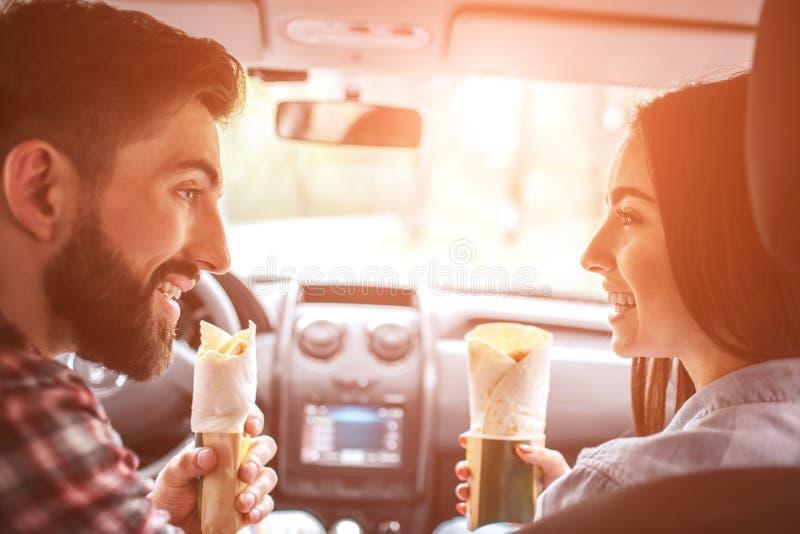 Os povos bonitos estão sentando-se junto no carro e estão olhando-se entre si Guardam rolos da galinha em no sua mão e sorriso imagem de stock royalty free