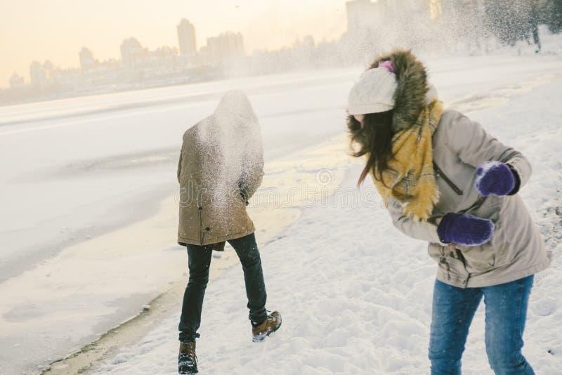 Os povos caucasianos novos em pares heterossexuais do amor têm uma data no inverno perto de um lago congelado Valentim ativo do f foto de stock royalty free