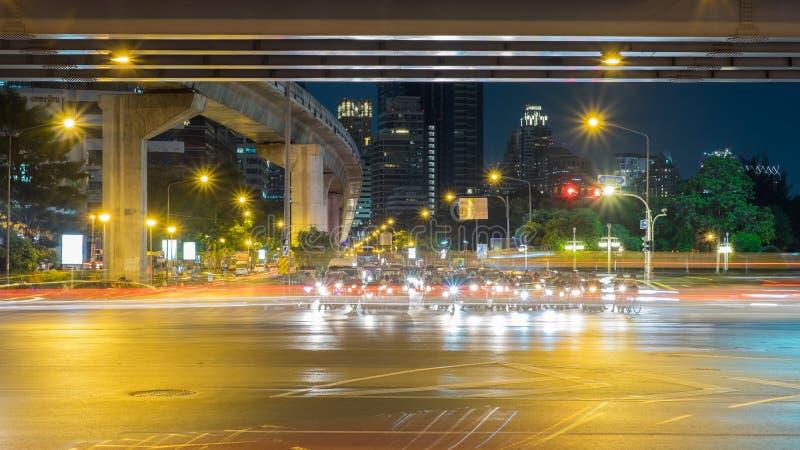 Os povos com veículos estão esperando para cruzar a rua na noite em Banguecoque, Tailândia fotos de stock royalty free