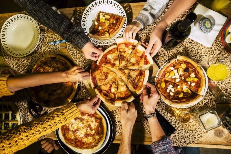 Os povos comem a pizza na tabela festiva servida para o partido Os amigos comemoram com alimento da restaura??o na opini?o de tam imagens de stock royalty free