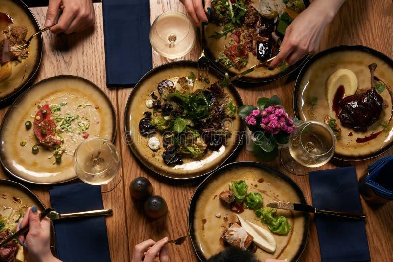 Os povos comem refeições saudáveis e a tabela festiva do álcool da bebida imagem de stock