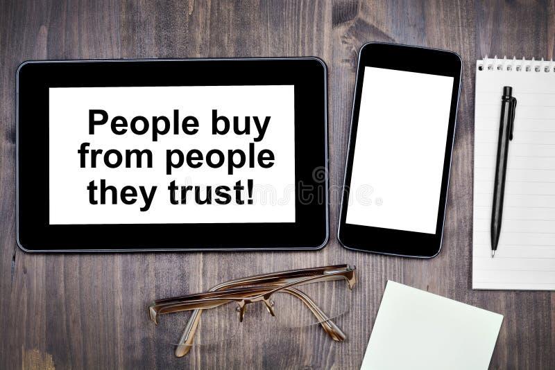 Os povos compram dos povos que confiam! Texto no dispositivo da tabuleta fotografia de stock royalty free