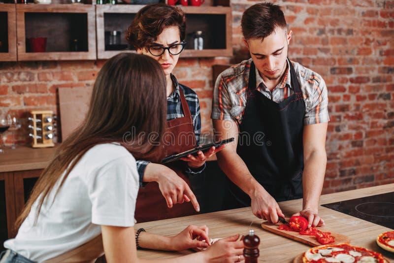 Os povos cozinham junto Amigos que têm o divertimento ao preparar a pizza fotografia de stock