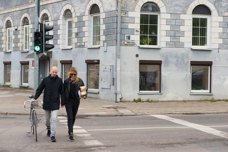Os povos cruzam a estrada no sinal em Vilnius, Lituânia foto de stock