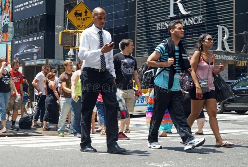 Os povos cruzam a rua em New York City imagem de stock