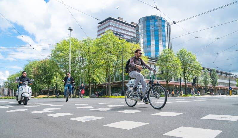 Os povos dão um ciclo e ciclos de motor através da interseção da cidade imagem de stock