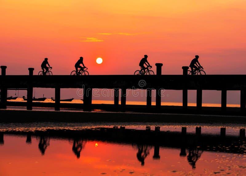 Os povos da silhueta estão dando um ciclo na noite foto de stock