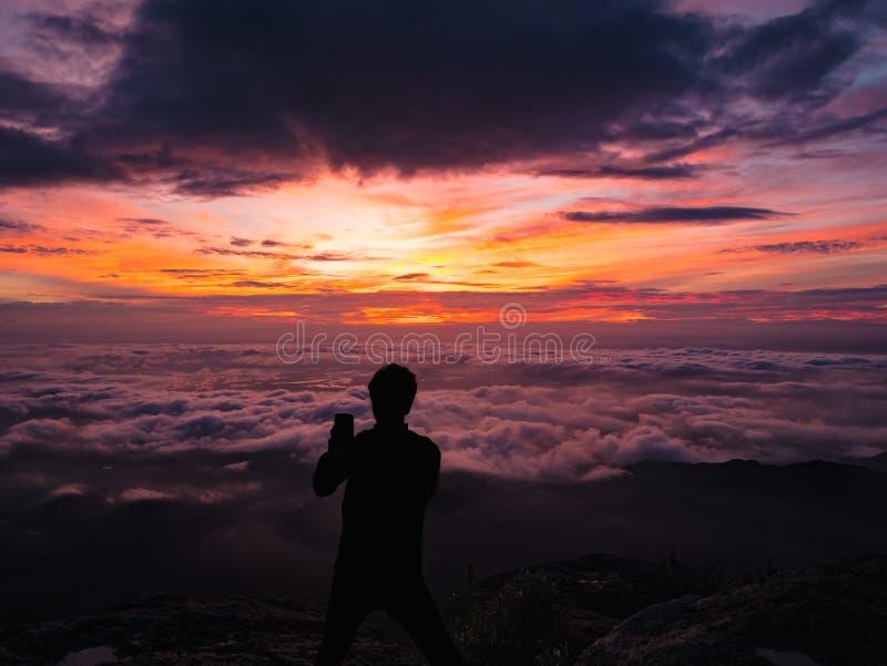 Os povos da silhueta tomam um Selfie no penhasco com o céu bonito do nascer do sol na montanha de Khao Luang fotografia de stock