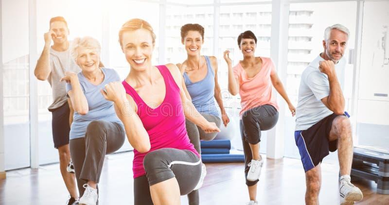 Os povos de sorriso que fazem a aptidão do poder exercitam na classe da ioga imagens de stock royalty free