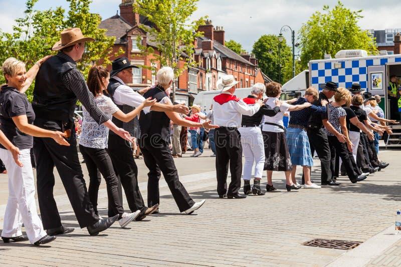 Os povos de todas as idades alinham a dança na rua imagens de stock