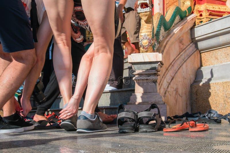 Os povos decolam suas sapatas antes de entrar no templo budista Conceito de observar tradições Conformidade com as regras fotos de stock