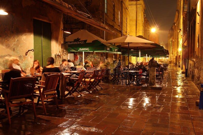 Os povos descansam na barra ao ar livre na noite fotografia de stock