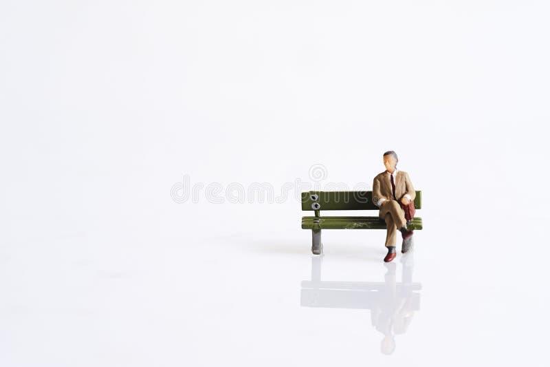 Os povos diminutos sentam-se no banco fotografia de stock royalty free