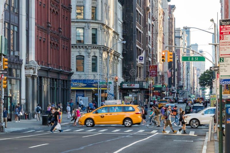 Os povos e os carros cruzam a interseção ocupada de Broadway e de 8a rua em Manhattan, New York City em 2017 fotos de stock