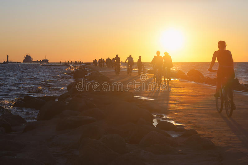Os povos em bicicletas montam ao longo do dique no mar no por do sol imagens de stock royalty free