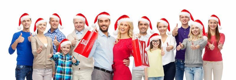 Os povos em chapéus de Santa com venda assinam no Natal fotografia de stock royalty free