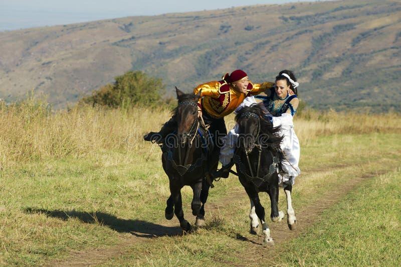 Os povos em vestidos nacionais montam a cavalo no campo, cerca de Almaty, Cazaquistão fotografia de stock