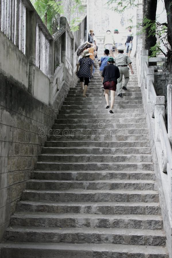 Os povos escalam as escadas velhas fotografia de stock royalty free