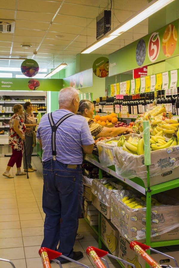 Os povos escolhem produtos no supermercado vegetal do departamento foto de stock
