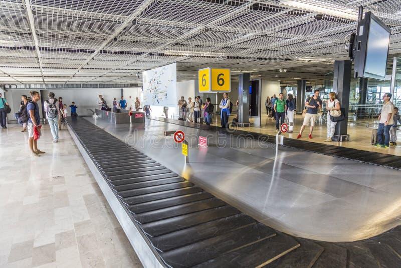Os povos esperam a bagagem no terminal de Marselha fotografia de stock