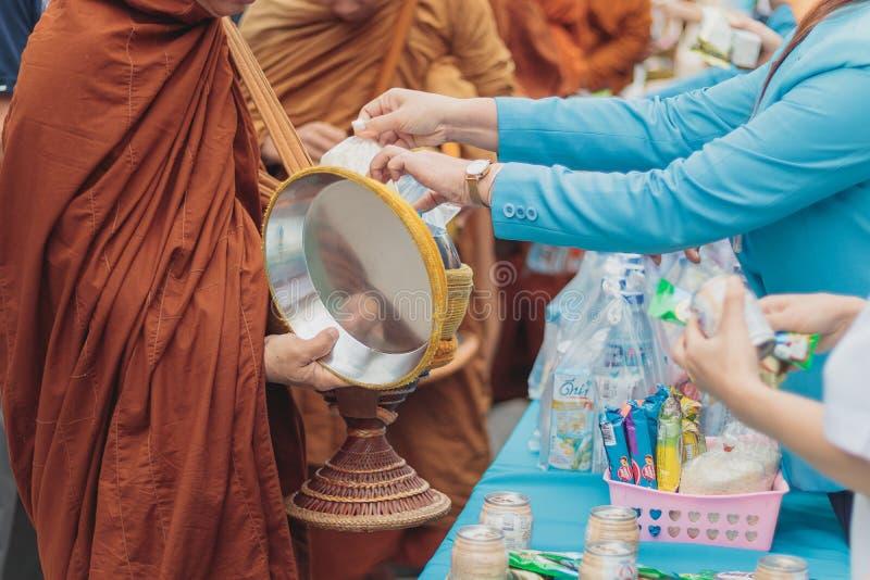 Os povos estão fazendo o mérito oferecendo o alimento e a água na esmola da monge rola na manhã, tradição budista fotografia de stock