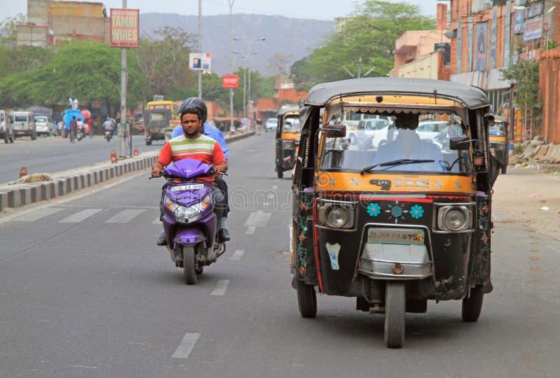 Os povos estão montando nos veículos pela rua em Jaipur, Índia fotografia de stock