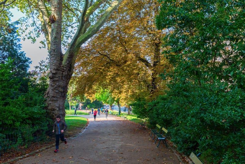 Os povos estão movimentando-se no parque Buttes Chaumont em Paris, França foto de stock